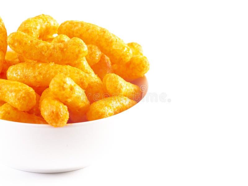 Soplos anaranjados del queso cheddar en un fondo blanco foto de archivo