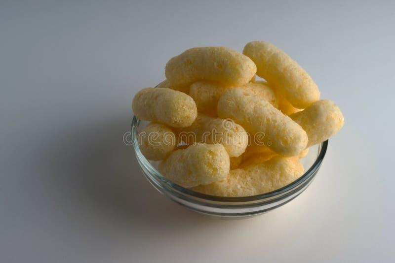 Soplos del maíz en un bol de vidrio Bocados soplados condimentados crujientes Partido, bocados de la película fotografía de archivo libre de regalías