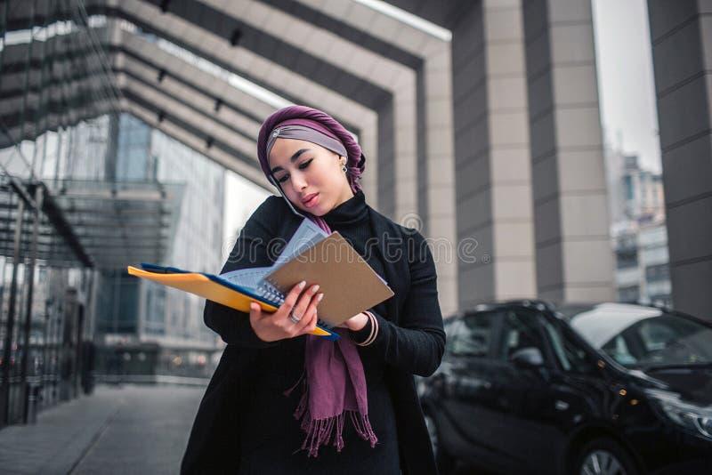 Soporte árabe joven ocupado de la mujer afuera Ella lleva a cabo el folde amarillo con los documentos y mirada abajo Negociacione imágenes de archivo libres de regalías