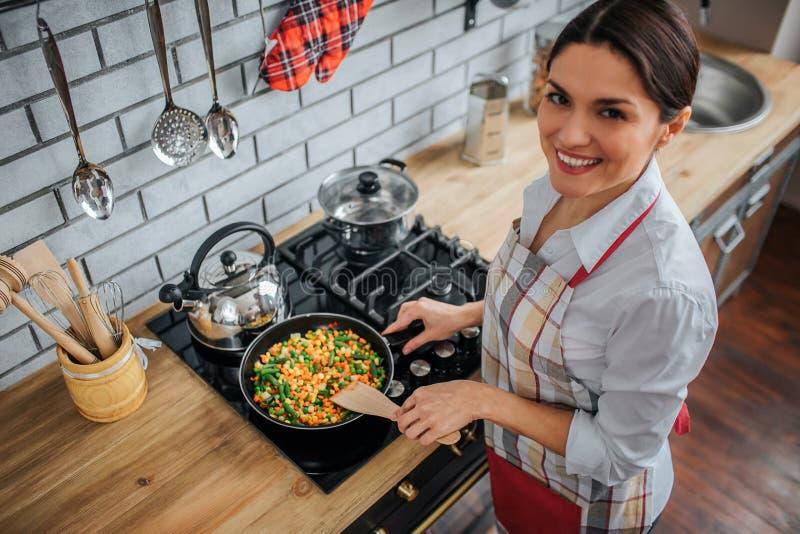 Soporte agradable alegre de la mujer adulta en cocina en la estufa Ella mira en cámara y sonrisa Verduras que fríen modelo en la  foto de archivo