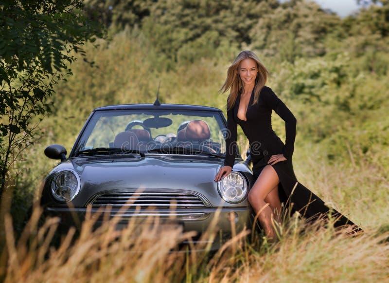 Soporte atractivo de la mujer cerca a un cabrio en vestido largo fotos de archivo
