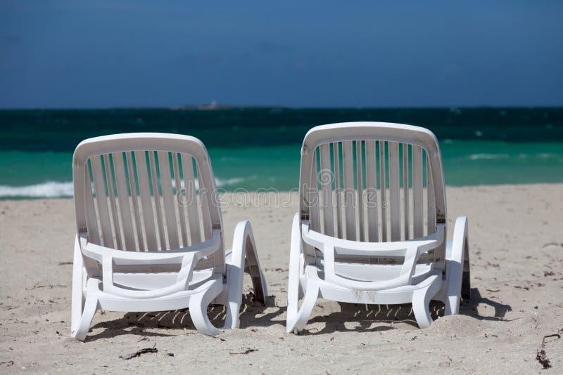 Soporte blanco de dos sillas de playa en frente de mar fotografía de archivo