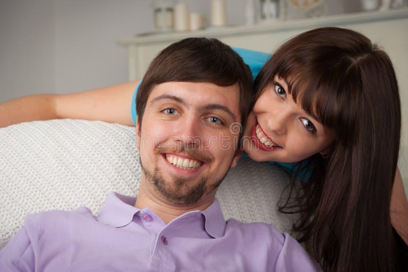 Soporte bonito joven de la mujer detrás de su novio que se sienta en el cou imágenes de archivo libres de regalías