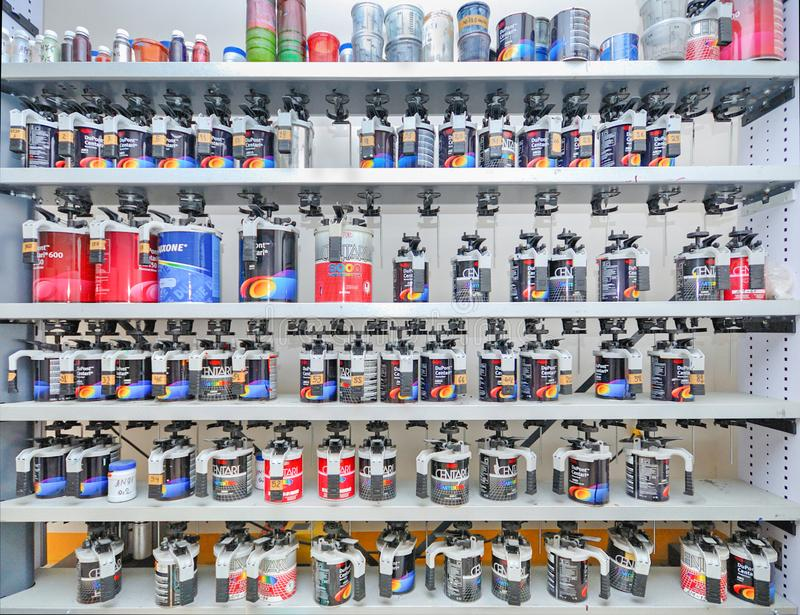 Soporte con una variedad de pinturas profesionales para los coches de pintura en el taller de reparaciones auto imagen de archivo libre de regalías