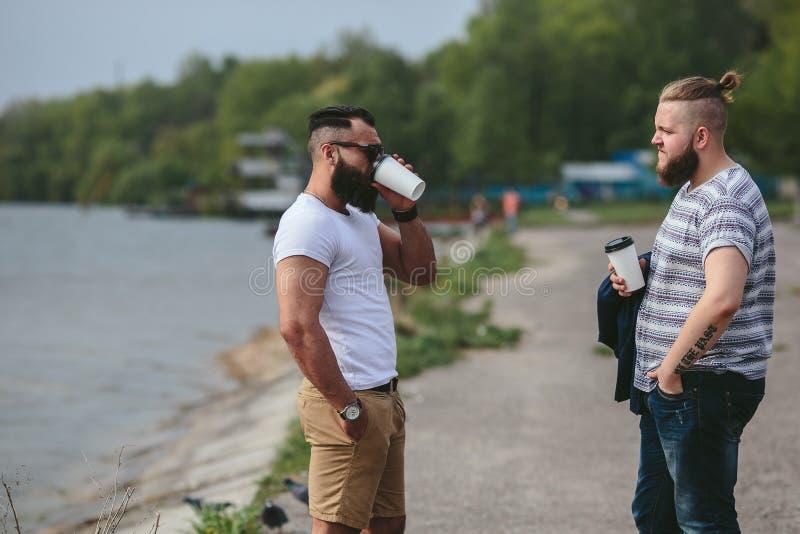 Soporte de dos hombres y café de la bebida fotos de archivo libres de regalías