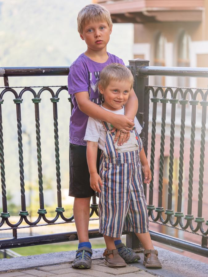 Soporte de dos niños pequeños que abraza en la puesta del sol imagenes de archivo