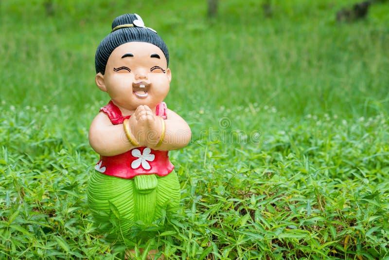 Soporte de la muñeca de la cerámica del bebé de la sonrisa entre verde foto de archivo libre de regalías
