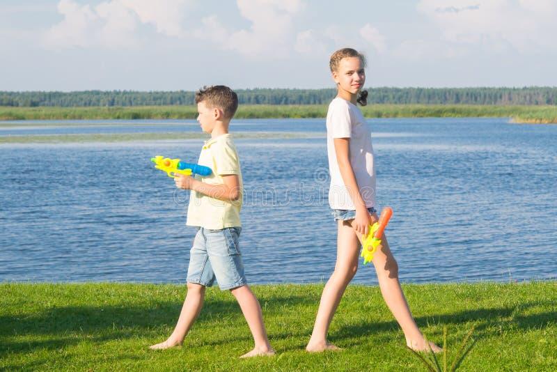 Soporte de la muchacha y del muchacho en la hierba verde, sus partes posteriores el uno al otro y jugar con las pistolas de agua, imagen de archivo libre de regalías