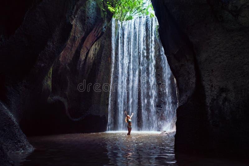 Soporte de la mujer debajo de la cascada de la cueva imagen de archivo libre de regalías