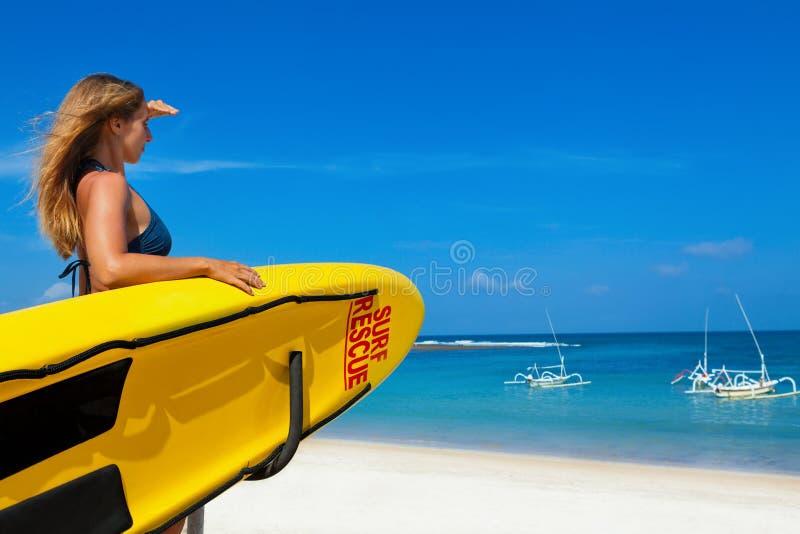 Soporte de la mujer del salvavidas con el tablero del rescate de la resaca en la playa foto de archivo