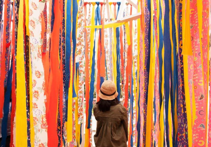 Soporte de la mujer joven con el fondo vibrante colorido de la tela foto de archivo libre de regalías