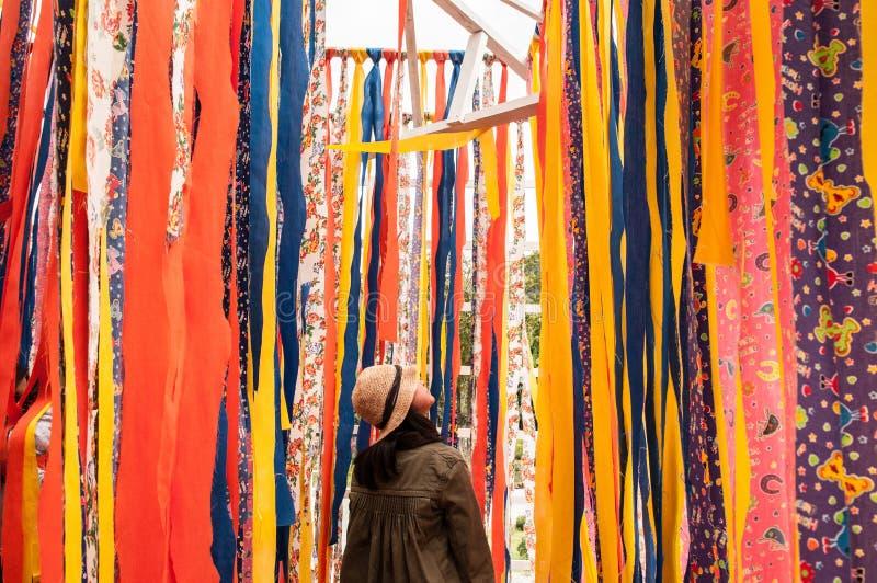 Soporte de la mujer joven con el fondo vibrante colorido de la tela imagenes de archivo