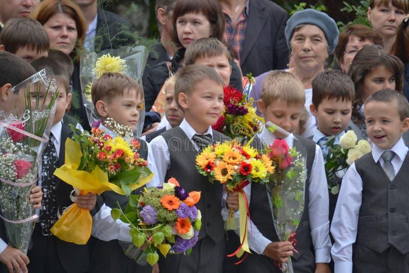 Soporte de los estudiantes de la escuela con las flores en manos fotos de archivo libres de regalías