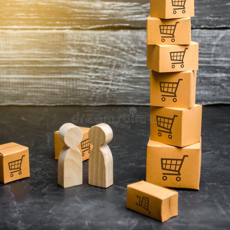 Soporte de madera de dos personas cerca de una torre de cajas comprador y vendedor, fabricante y minorista Negocio y comercio foto de archivo
