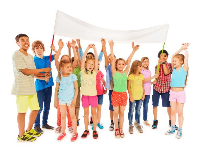 Soporte de muchos niños con la bandera en blanco imagen de archivo libre de regalías