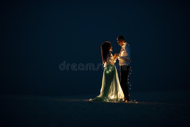 Soporte de novia y del novio, manos del control y mirada en uno a en desierto al lado de la guirnalda de bombillas en la noche foto de archivo