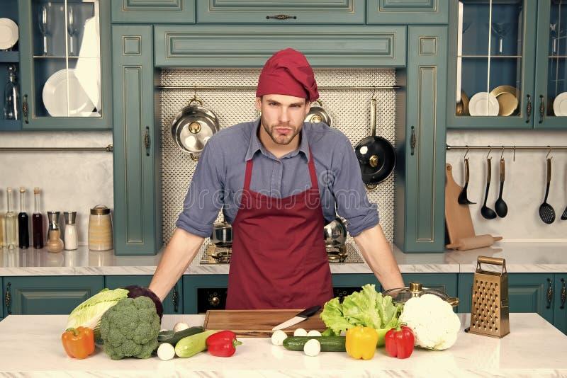 Soporte del cocinero en la tabla de cocina Hombre en sombrero del cocinero y delantal en cocina Verduras y herramientas listas pa imágenes de archivo libres de regalías