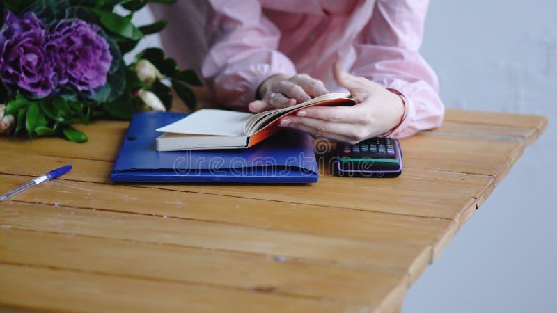 Soporte del florista detrás del contador y leído un cuaderno en floristería imágenes de archivo libres de regalías