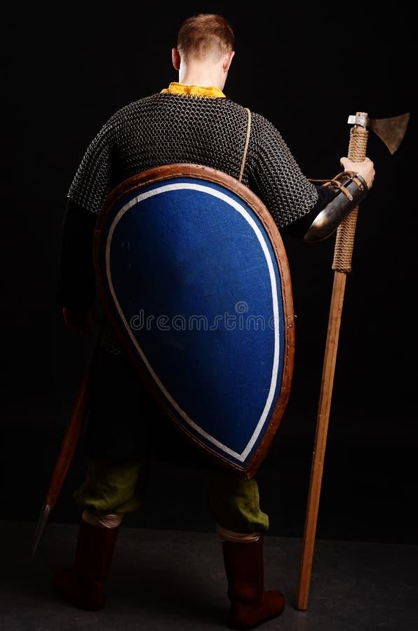 Soporte del guerrero el suyo de nuevo a la cámara con un escudo en el suyo parte posterior a fotografía de archivo libre de regalías