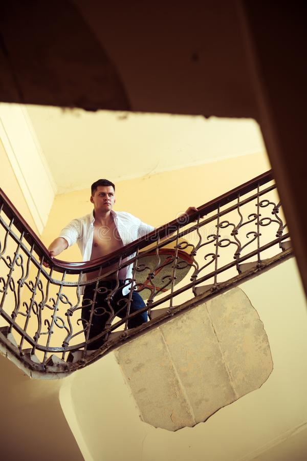 Soporte del hombre alto en escalera Escaleras de la subida del hombre de negocios Machista atractivo en camisa abierta con el tor imagenes de archivo