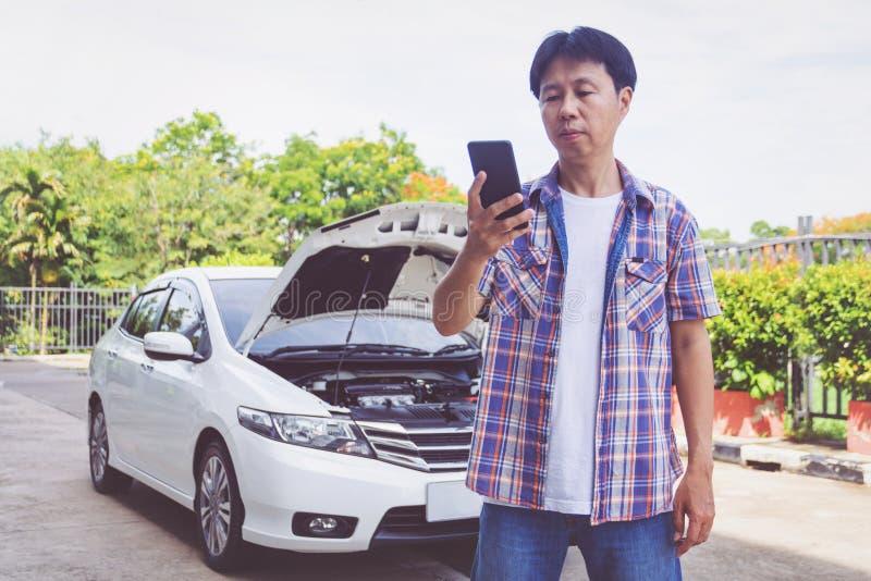 Soporte del hombre de Asia delantero un coche quebrado que llama para la ayuda fotografía de archivo