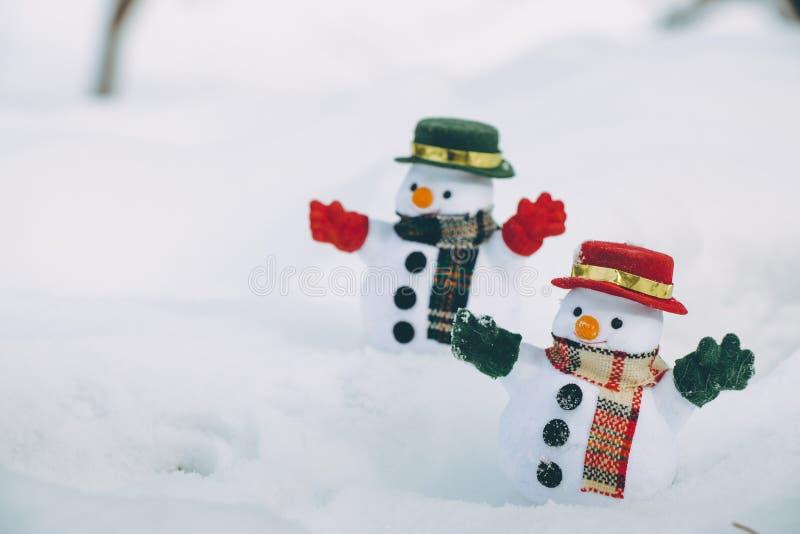 Soporte del hombre de la nieve dos entre la pila de nieve en parque La sol es warmi imagen de archivo libre de regalías