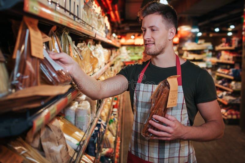 Soporte del hombre joven en el estante de las pastas en colmado Él puso el empaquetado en él del estante y de la sonrisa Trabajad fotos de archivo libres de regalías