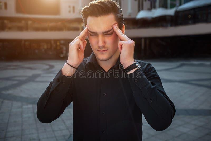 Soporte del hombre joven exterior y sostener los fingeres en la plomada Él mantiene ojos cerrados Es exterior soleado imágenes de archivo libres de regalías