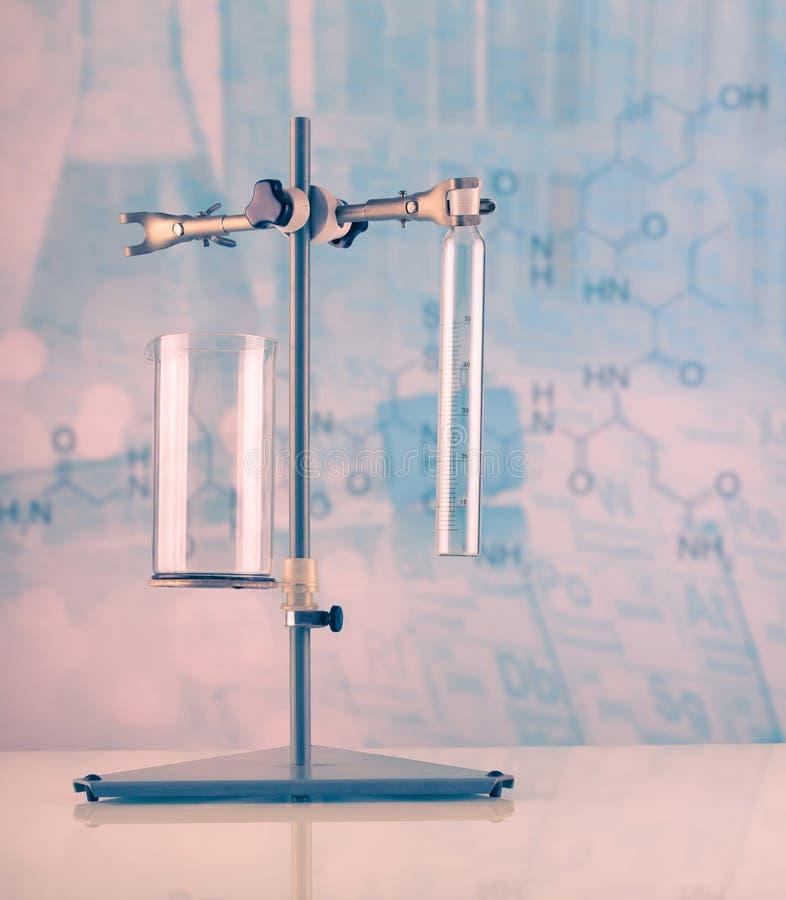Soporte del laboratorio con una variedad de frascos y de buques en azul claro foto de archivo