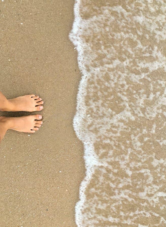 Soporte del pie en el arena de mar y venir de la onda de la espera, superiores abajo de la visión imagen de archivo