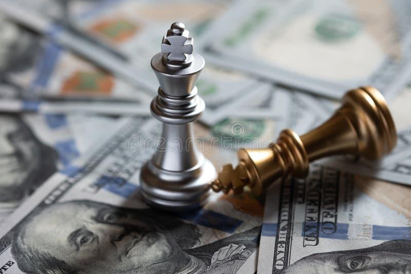 Soporte del rey del ajedrez sobre enemigo caido en fondo del billete de banco de los E.E.U.U. La inclinaci?n y la explotaci?n agr imagen de archivo libre de regalías