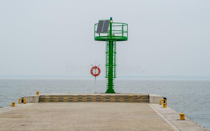 Soporte del salvavidas y un jefe portuario verde en un pequeño puerto imagen de archivo