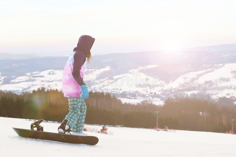 Soporte del snowboarder de la muchacha en el fondo de montañas coronadas de nieve, preparándose para el eslalom Equipo de deporte imagen de archivo