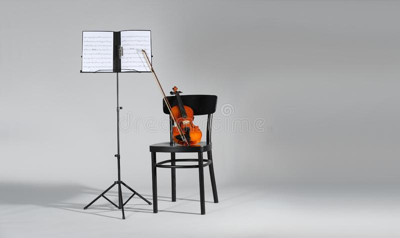 Soporte del violín, de la silla y de la nota con las hojas de música en fondo gris imágenes de archivo libres de regalías