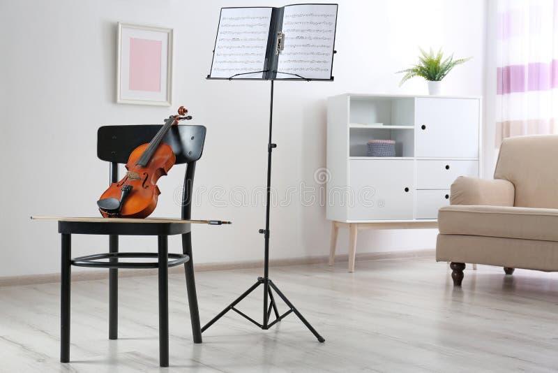 Soporte del violín, de la silla y de la nota con las hojas de música fotografía de archivo libre de regalías
