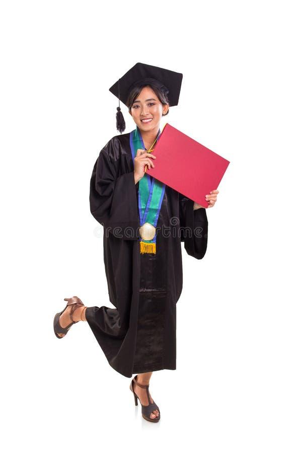 Soporte feliz del estudiante de graduación con una pierna para arriba, en el fondo blanco fotografía de archivo