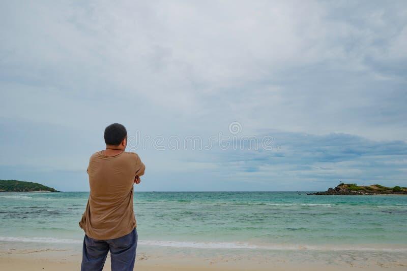 Soporte gordo asiático del viajero en la playa idílica con el cielo hermoso en tiempo de vacaciones foto de archivo libre de regalías