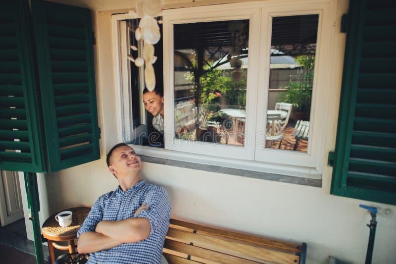 Soporte hermoso joven de los pares cerca del abrazo de la ventana, sonrisa feliz hola fotografía de archivo