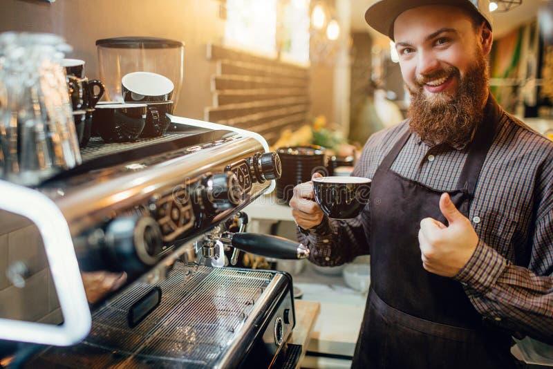 Soporte joven agradable y positivo del barusta en cocina en la máquina del café Él detiene el pulgar grande y la taza de café Son imagen de archivo