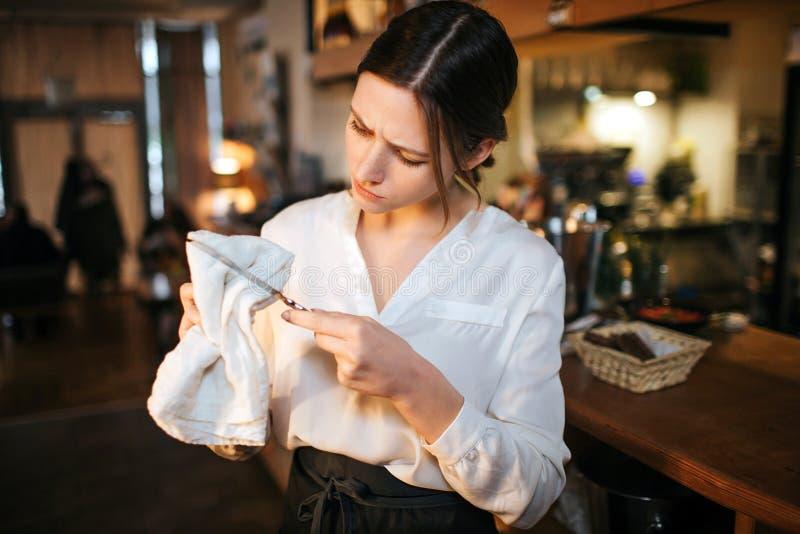 Soporte joven ocupado de la camarera en el cuchillo de la barra y del trapo Ella lo mira seriamente Trabajo de la mujer de Yougn  foto de archivo