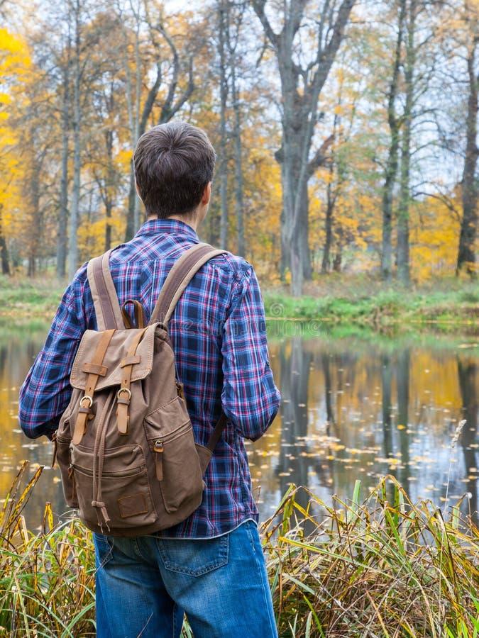 Soporte masculino del caminante cerca del lago del otoño foto de archivo