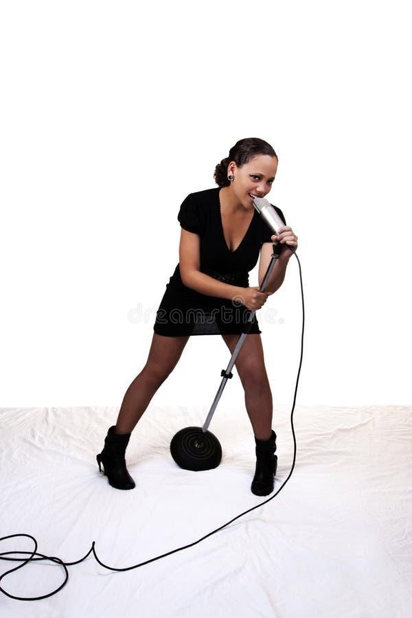 Soporte mezclado joven del micrófono del canto de la mujer negra imagen de archivo libre de regalías