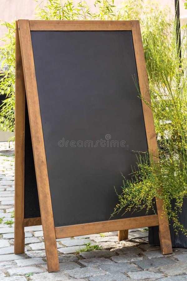 Soporte negro de la pizarra en la madera para un menú del restaurante en el stre fotos de archivo libres de regalías