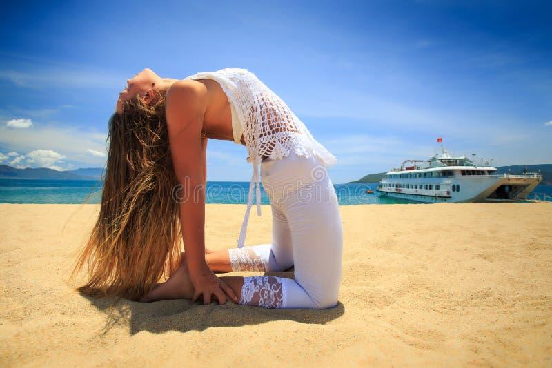 soporte rubio de la muchacha en camello de la curva de la parte posterior del asana de la yoga en la playa imagenes de archivo
