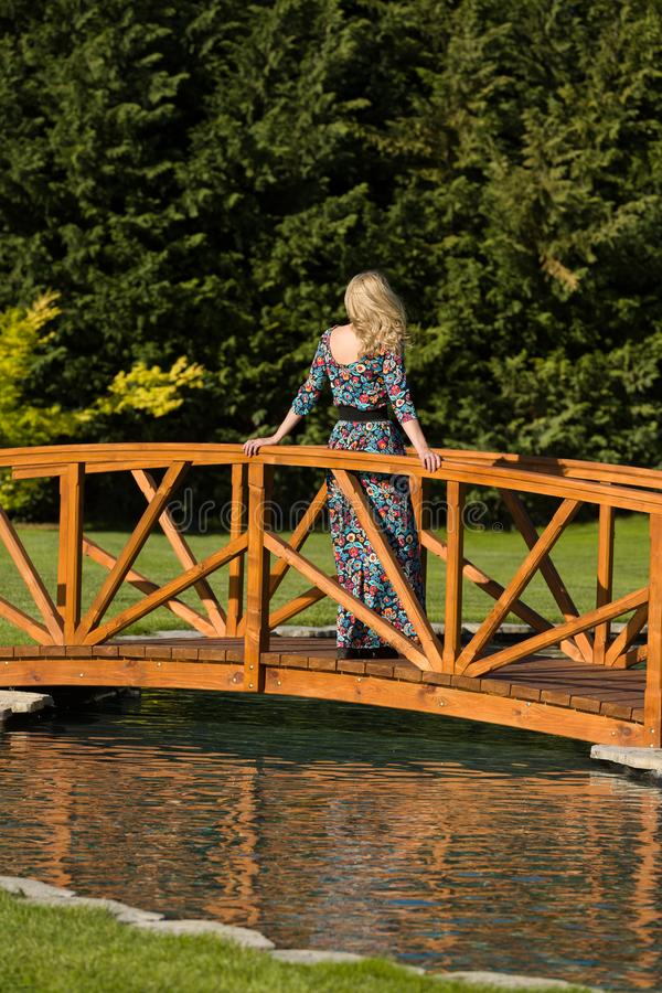 Soporte rubio de pelo largo hermoso de la mujer en un puente de madera sobre una charca artificial, en anillo natural, fondo verd foto de archivo libre de regalías