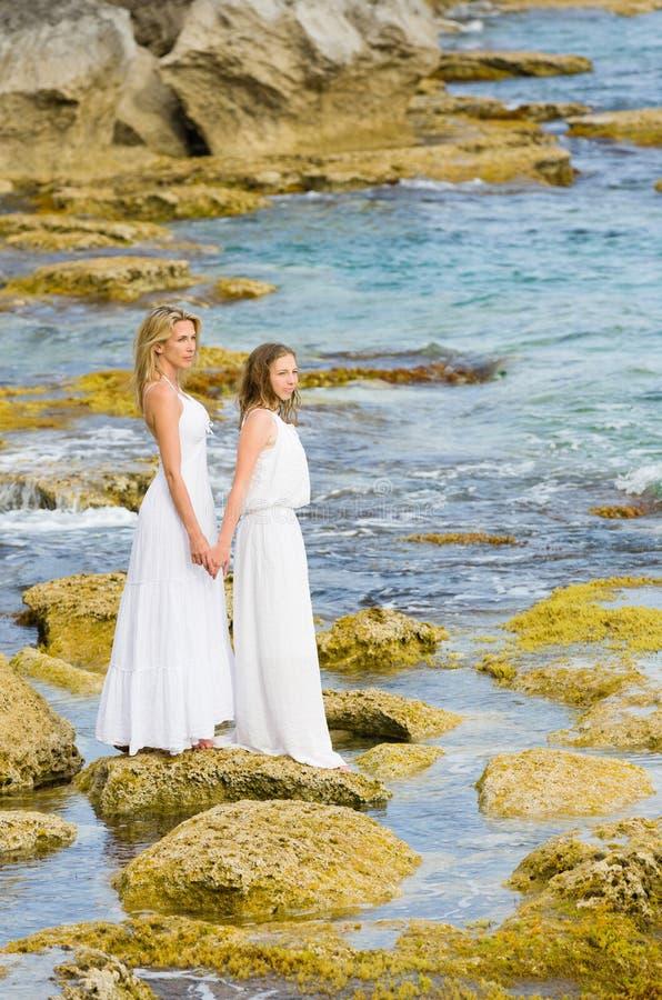 Soporte rubio hermoso de la madre y de la hija en rocas costeras en el vestido largo blanco imagenes de archivo