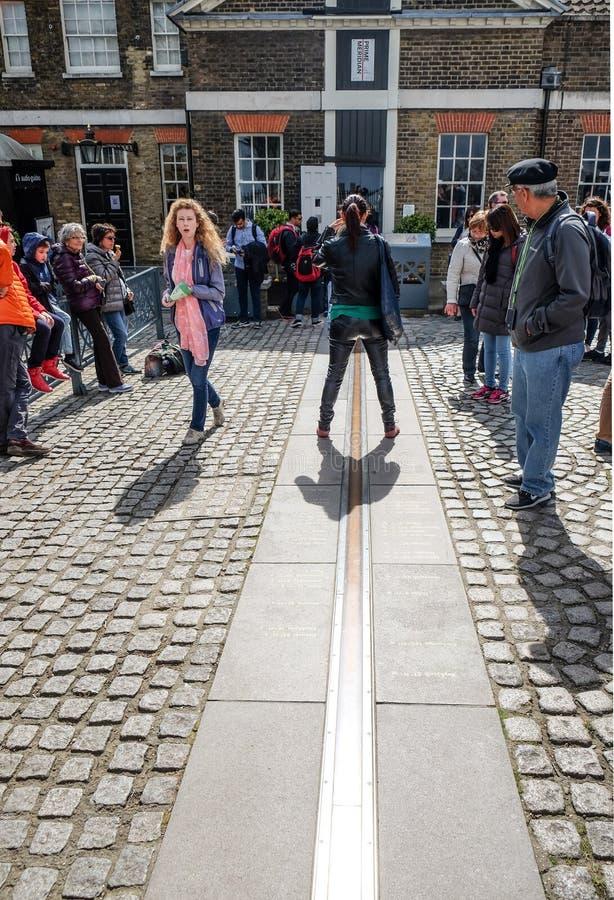 Soporte turístico entre el este y al oeste de la línea del meridiano primero en el observatorio real Greenwich Greenwich es notab fotografía de archivo libre de regalías