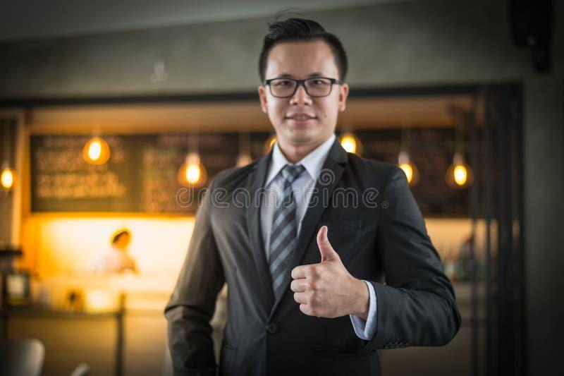 Soporte y sonrisa asiáticos del hombre de negocios, él muestra el pulgar para arriba en la oficina Concepto acertado del negocio fotos de archivo libres de regalías
