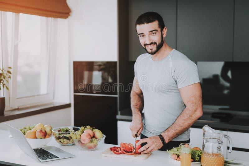 Soportes atléticos del hombre en cocina Cocinar concepto foto de archivo