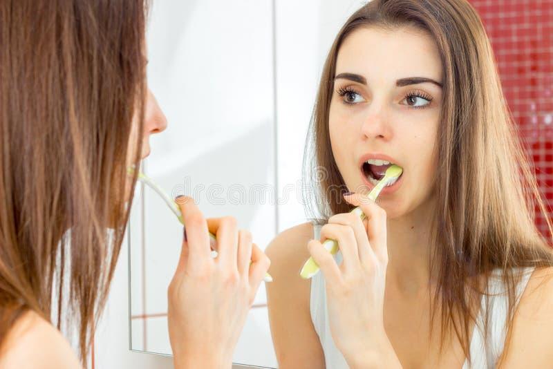 Soportes atractivos de la chica joven en las miradas del cuarto de baño en el espejo y el cepillado de sus dientes cepillados imagen de archivo libre de regalías